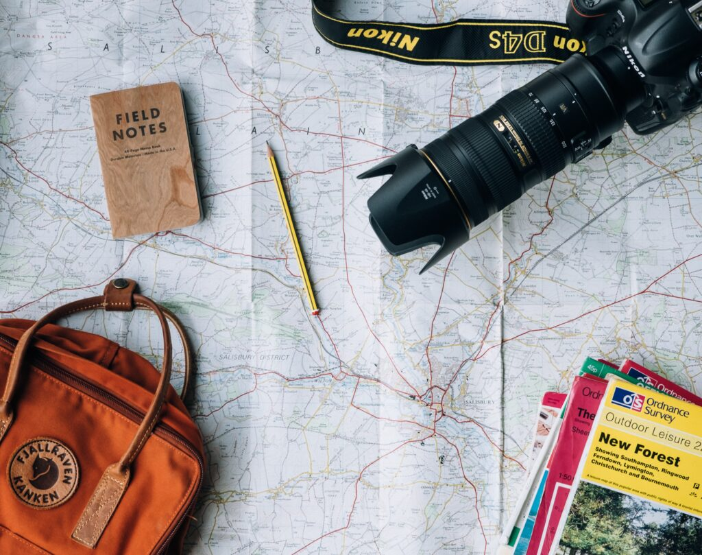 flat lay of map with camera, pencil, notebook, and travel accessories